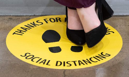 A woman's shoes on top of a social distancing sign.